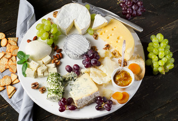 Fototapete - Cheese plates served with grapes, jam,  and nuts on a wooden board.