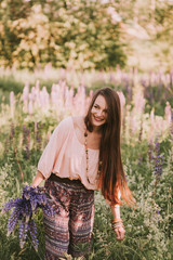 Young beautiful brown hair hippie girl holding a bouquet of purple flowers in hands, gathering flowers in fields. Walking in evening meadow. Outdoors