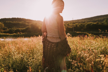 Young brunette woman standing in the sunlit evening field wearing bo ho clothes. Attractive girl in sunset. Girl walking in meadow in evening. Outdoor