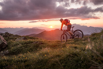 Male mountainbiker at sunset in the mountains Wall mural