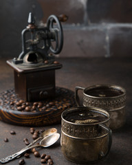 Two old vintage cups of coffee with cocoa beans, old coffee grinder and old spoons on dark brown surface opposite the dark brick wall. Still life. Coffee break