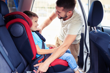 Small son in car seat being put in back of car by father