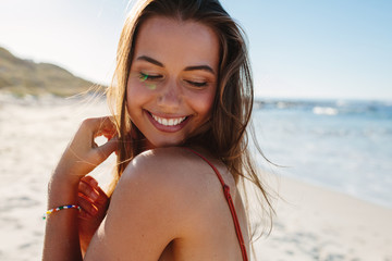Smiling young woman on the beach.
