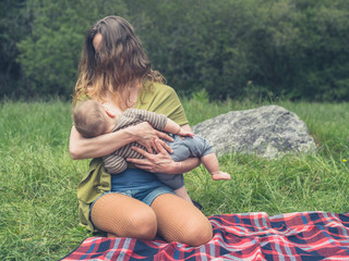 Young mother breastfeeding her baby in nature