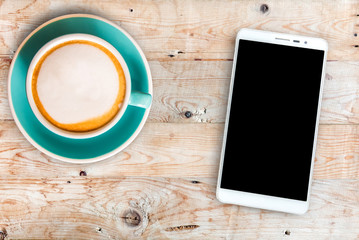 Top view Smart phone and Black coffee in a white cup on Wooden table.
