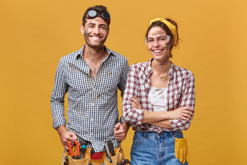Horizontal studio shot of two happy confident repairmen in protective wear standing next to each other at blank wall and smiling broadly at camera, ready for repairing, fixing and renovating Wall mural