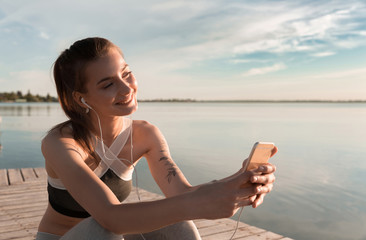 Young smiling sports lady at the beach listening music