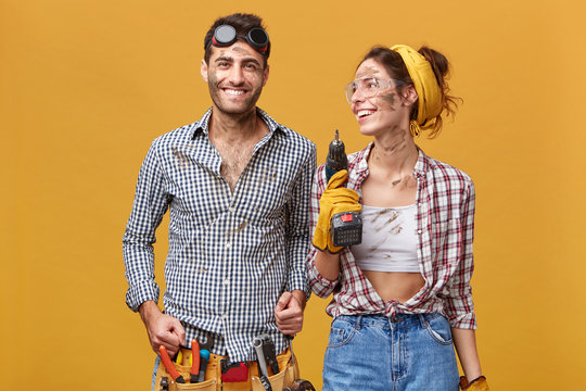 People, job, profession, occupation, teamwork and success concept. Team of maintenance staff enjoying results of their common work: beautiful woman with drill looking at man and smiling happily