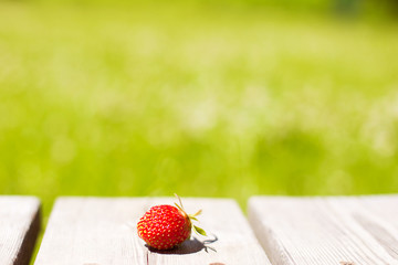 strawberries on a wooden background. Strawberry against the background of the green grass