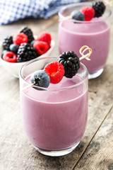 Healthy berry smoothie in glass on wooden table