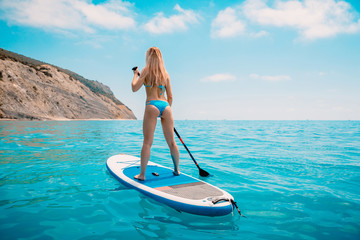 Young slim woman in bikini on stand up paddle board and blue sea