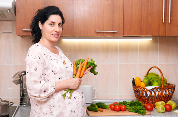 pregnant woman in kitchen interior with fresh fruits and vegetables, healthy food concept