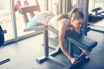 Woman workout in gym. Young woman doing exercises for the stomach.