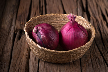 Ripe red onion on wooden background.