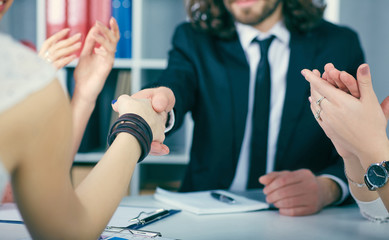 Close up businessmen handshake on team meeting with clapping group of people in background at modern startup business office interior.
