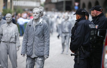 "Participants in the so called ""1000 Figures"" demonstration perform near German police before the upcoming G20 summit in Hamburg"