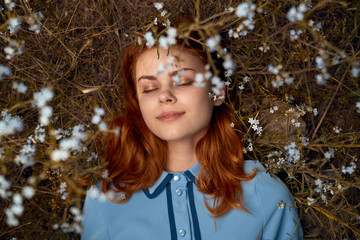 Beautiful young woman lies in flowers in a field