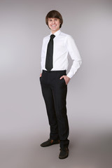 Cheerful employee man in white shirt with black tie keeping hands in pockets and smiling while standing isolated grey studio background.