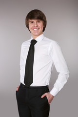 Handsome man in white shirt with black tie keeping hands in pockets and smiling while standing isolated grey studio background.