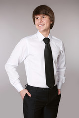 Student Man in white shirt with black tie keeping hands in pockets and smiling while standing against grey studio background.