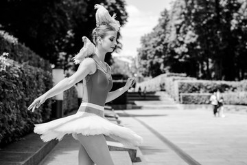 Young beautiful ballerina with two white birds dove of peace in a city park
