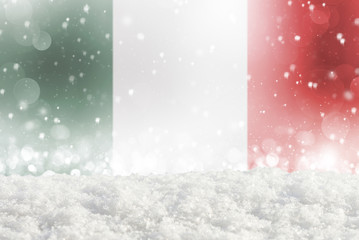 Defocused Italy flag as a winter Christmas background with falling snow, snowdrift and bokeh