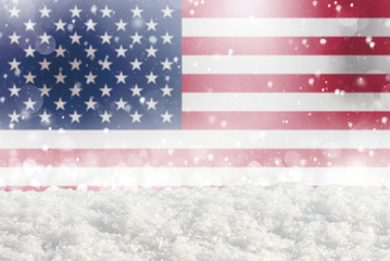 Defocused American flag as a winter Christmas background with falling snow, snowdrift and bokeh