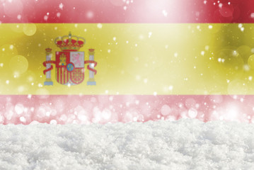 Defocused Spain flag as a winter Christmas background with falling snow, snowdrift and bokeh