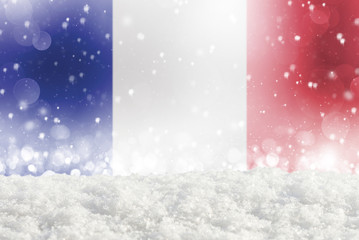 Defocused France flag as a winter Christmas background with falling snow, snowdrift and bokeh