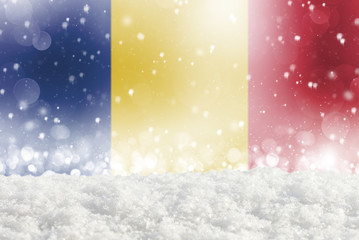 Defocused Romania flag as a winter Christmas background with falling snow, snowdrift and bokeh