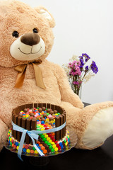 Happy birthday cake and big Teddy Bear. Festive tea party. Pinata Cake, a celebration cake with a hidden stash of sweets inside.