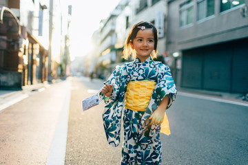 Mixed race girl in traditional Japanese costume on street