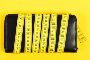 Wallet in black color wrapped around with striking yellow tape