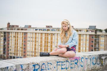 Young beautiful blonde caucasian girl listening music