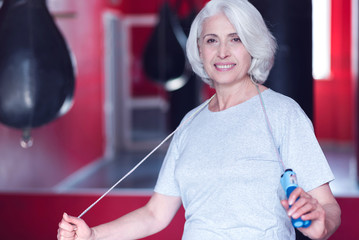 Nice senior lady standing with skipping rope