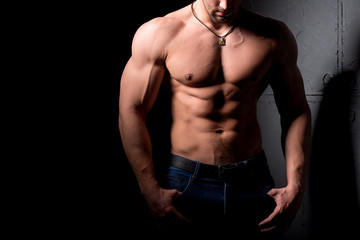 Fitness concept. Muscular and sexy torso of young man having perfect abs, bicep and chest. Male hunk with athletic body.