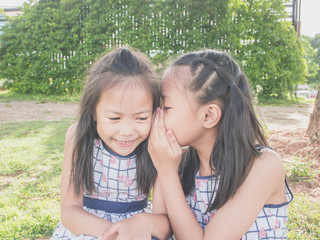 Beautiful girl whispered something to her sister in the park. Her sister looked very happy.