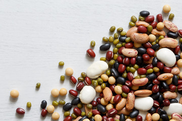 Mixed dry beans on white wooden board from above. Space for text.