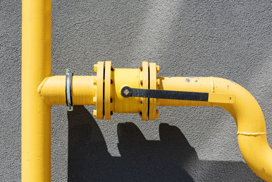 yellow metal gas pipeline with valve on background of wall