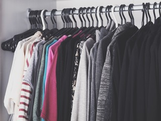 Woman's color-coordinated closet full of fashionable trendy clothes like t-shirts, blouses, sweaters, blazers, shirts and jackets.