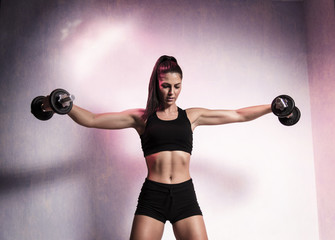 Attractive muscular young woman doing shoulder exercise with dumbbells