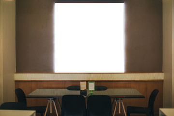 Black frame with a white background hanging on a wooden wall in a restaurant.