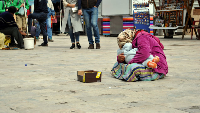 Shamed homeless woman with child in her hands is begging for the money on the street; people and poverty concept.