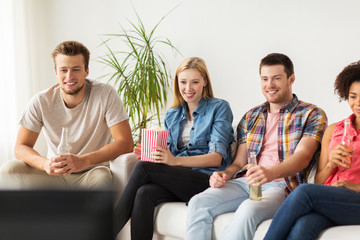 happy friends with popcorn watching tv at home