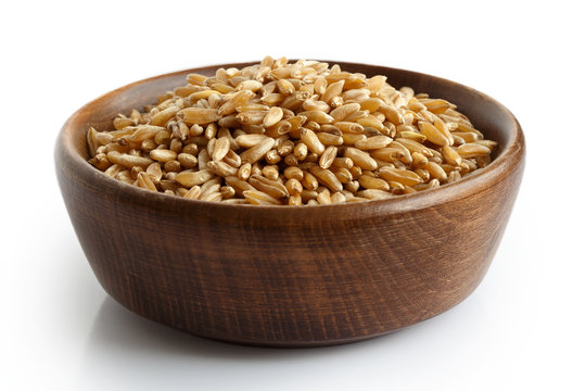 Kamut wheat kernels in dark wooden bowl isolated on white.