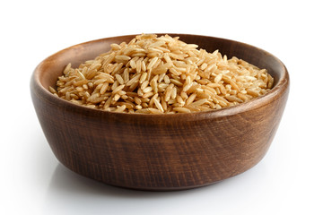 Uncooked long grain brown rice in dark wooden bowl isolated on white.
