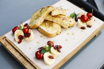 Fried bread with sugar with decoration of chopped banana and cherries