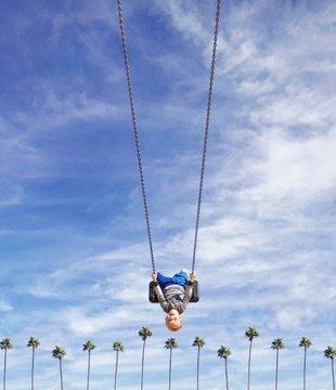 Boy swinging upside down on a swing over a row of palm trees, Orange County, California, America, USA