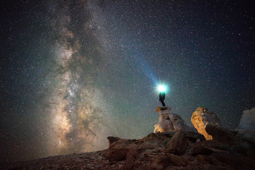 Man with illuminated headlamp standing on rock against milky way
