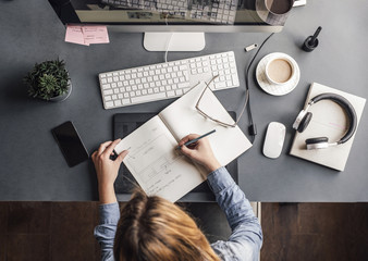 Overhead photo of businesswoman writing in notebook at office.